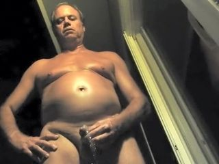 Nude parent taking a urinate at night outdoors.